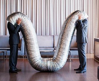 Zwei Männer schauen in eine große silberne Röhre