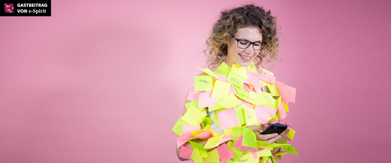 Frau schaut auf Handydisplay. Sie ist übersäht mit Post-it Klebezetteln.